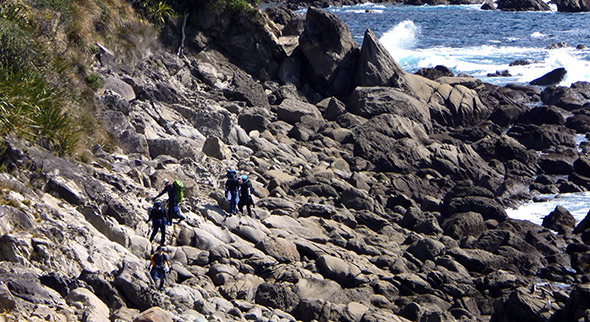 The film crew lugging their gear across the rocks